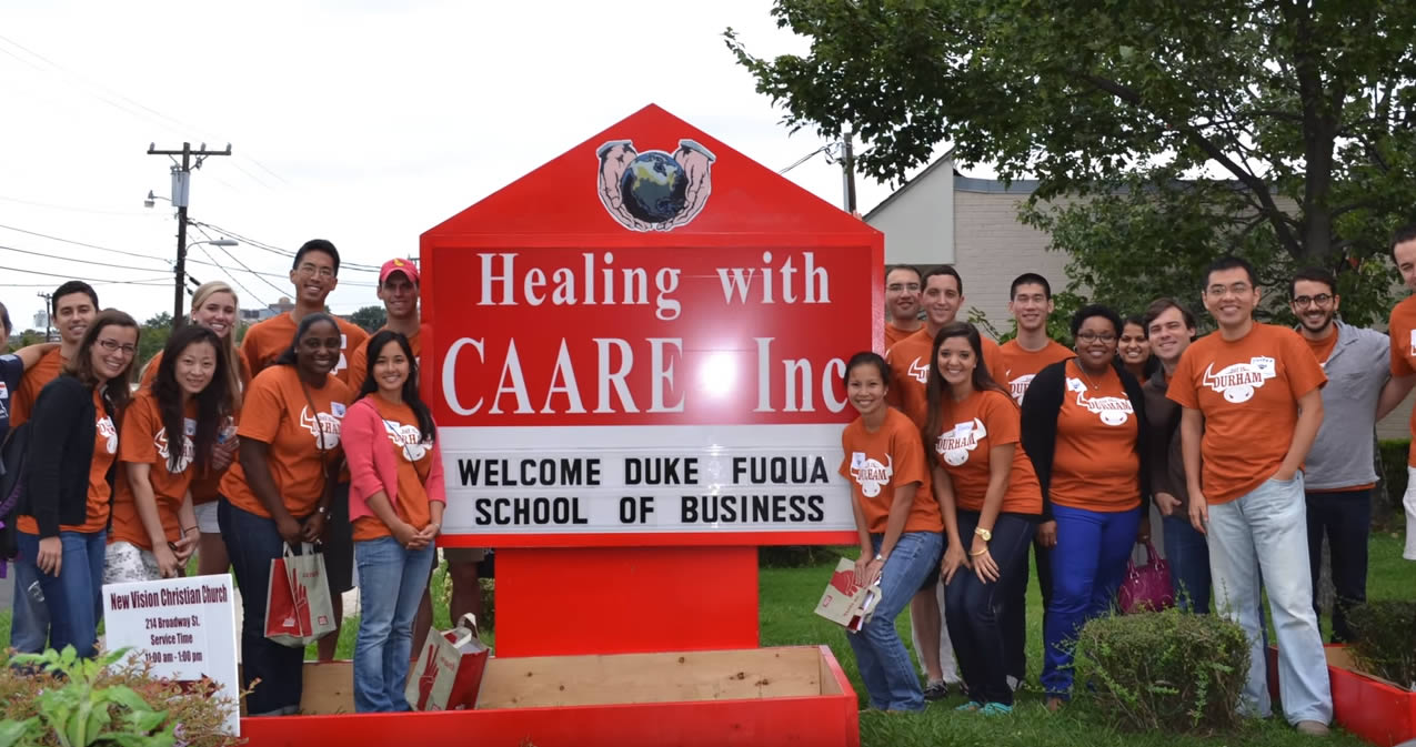 Fuqua students at Healing with CAARE Inc. sign