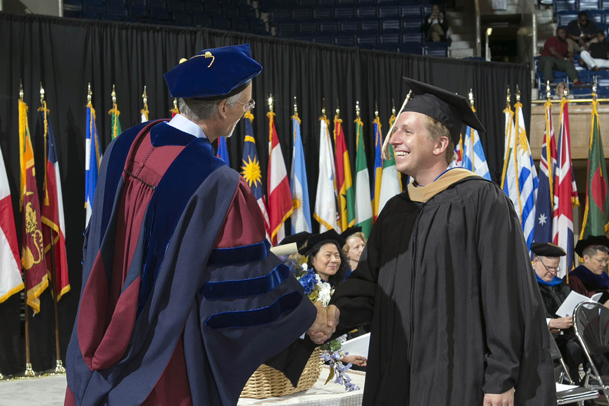 a graduate shakes Dean Bill Boulding's hand on the commencement stage