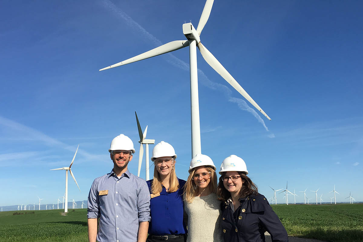 Four students wearing hardhats in a wind farm