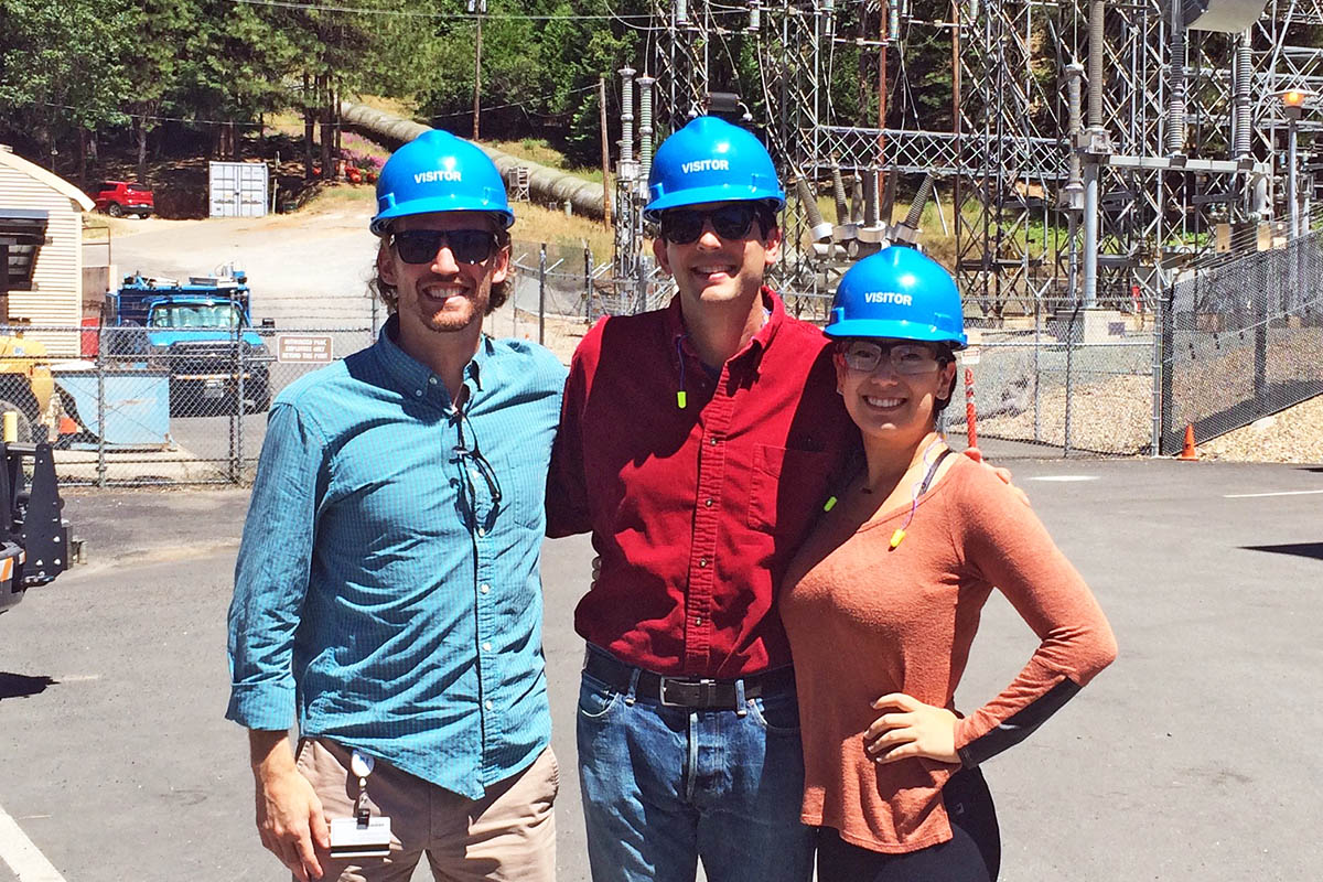 Three Fuqua students in hard hats at a utility company